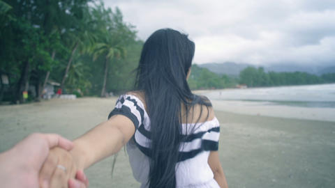 Pretty Girl with long hair walking at beach and holding her boyfriend's hand Live Action