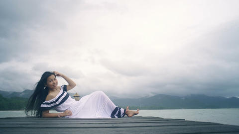 Thai Girl in white dress laying on wooden pier Live Action