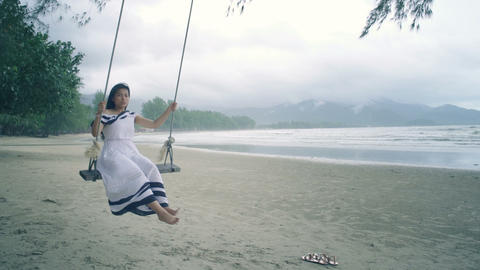 Thai Girl in white dress swinging on a swing at beach Live Action