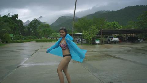 Young Thai Woman in bikini and raining coat Live Action