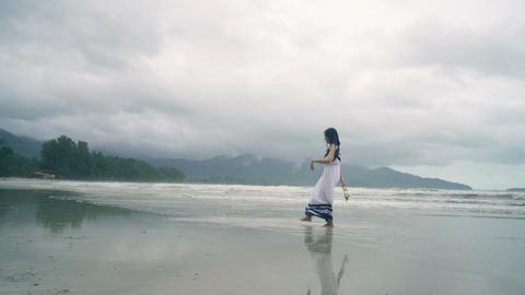 Young Woman in white dress kicks water at beach Live Action