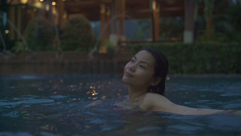 Happy Thai Girl having fun in a swimming pool at night Live Action