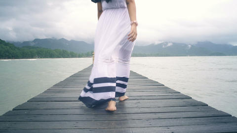 Young Woman with long hair walking on wooden pier Live Action