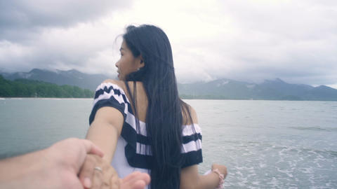 Pretty Girl with long hair walking on pier and holding her boyfriend's hand Live Action