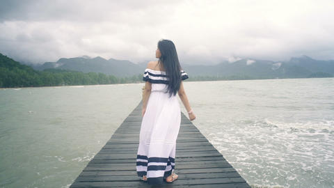 Smiling young Woman in white dress on wooden pier turning to camera Live Action