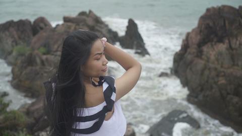 Yong Asian Woman with long hair looking at rocks and sea Live Action