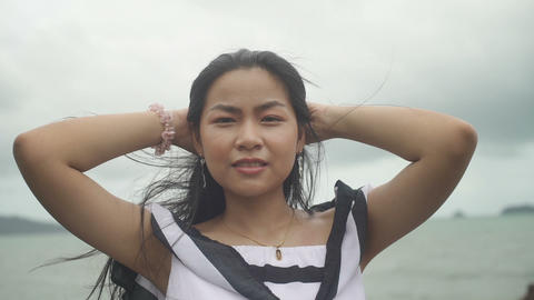 Portrait of yong Asian Woman and sea on background Live Action