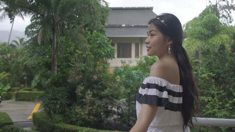 Pretty Thai Girl looking at tropical garden Live Action