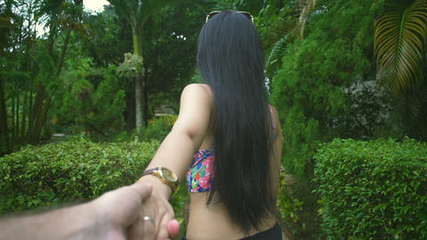 Asian Girl walking and holding her boyfriend's hand at tropical garden Live Action