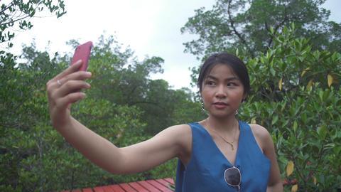 Thai Girl making selfie on smartphone in tropical garden Live Action