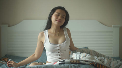 Young Thai Woman waking up in her bed and stretches Live Action