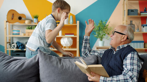 Playful child and loving grandfather doing high-five while old man reading book Live Action