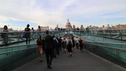 People walking over Millennium bridge London UK Footage