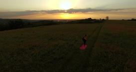 Aerial: low flight over young woman doing yoga in a field at sunset Footage