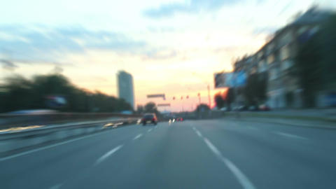 Dusk driving time lapse through city, cars with lights Footage