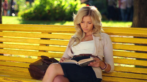 Young adult woman girl reads book in park yellow bench waiting Footage