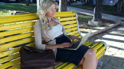Pretty girl sitting yellow bench typing, social network stedicam Footage