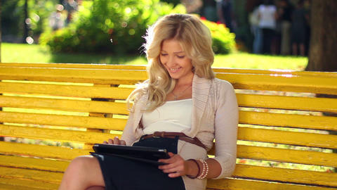 Pretty woman types message on tablet pc computer in park bench Footage