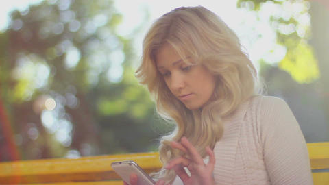 Woman types sms smiles sending message, daytime park bench Footage