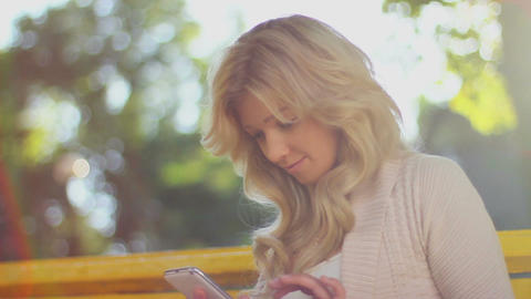 Touch phone sms writing, young woman girl in park bench Footage