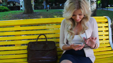 Happy business woman writes message on touch phone in park dolly Footage
