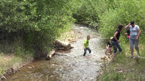 Children racing homemade rafts mountain creek 4K 022 Footage