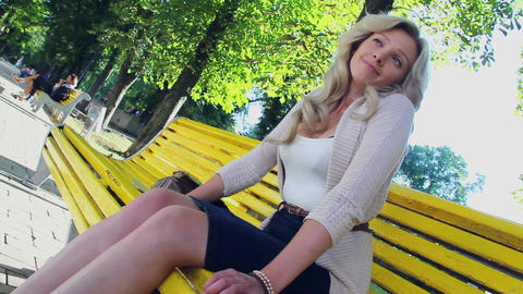 Smiling looking happy young woman in park on bench sitting grin Footage