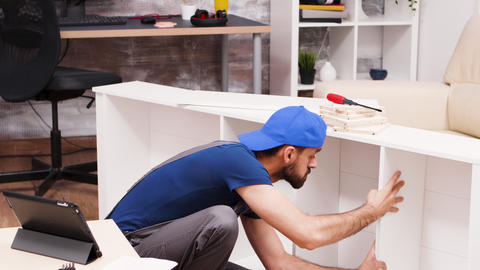 Attractive handyman assembles new furniture Live Action