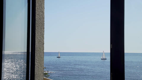 The view from the window on the yachts in the sea. Yachts with white sails. Sun glare on a light sea Live Action