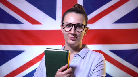 Beautiful girl student in glasses, with notebooks in a shirt, stands in front of Live Action