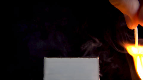 A man lights a match on a matchbox. A man holds a match in his hand and lights Live Action
