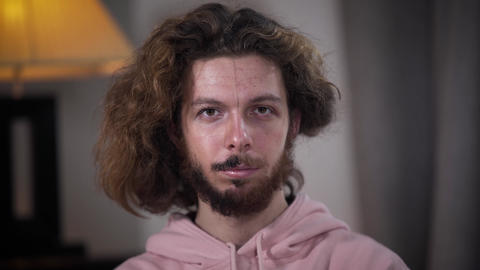 Close-up of bearded Caucasian man turning head, looking at camera, and turning Live Action