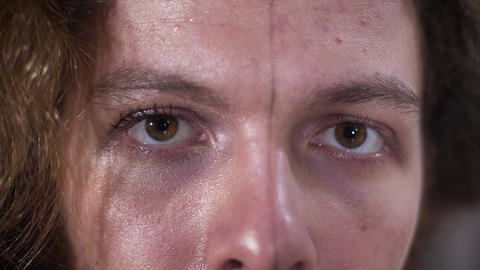Close-up of man's brown eyes. Face divided into two parts, feminine and Live Action