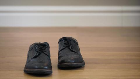 Black stylish broggi boots standing on wooden floor. Close-up of elegant leather Live Action