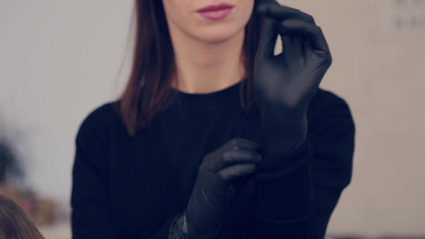 Makeup artist woman puts on rubber gloves before the procedure in a beauty salon GIF
