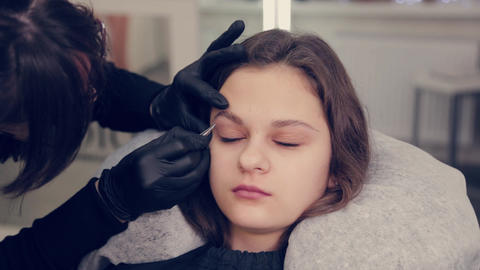 Professional master eyebrow woman plucking eyebrows with tweezers to client in Live Action