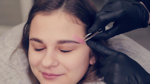 Professional master eyebrow woman doing depilation with wax eyebrow to client to Live Action