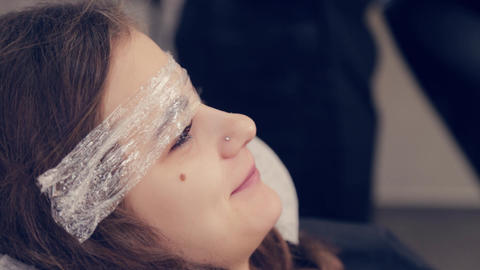 Beautiful young girl with a film on eyebrows in a beauty salon Live Action