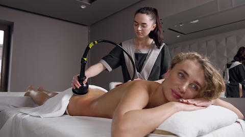 Pretty adult blond woman lying in on massage table and having anticellulite back Live Action