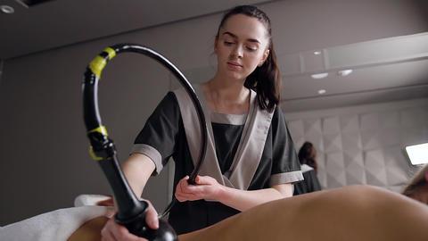 Attractive brunette girl-masseur making anti cellulite massage using lpg Live Action