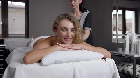 Front view of smiling charming blond woman which relaxing during body massage in Live Action