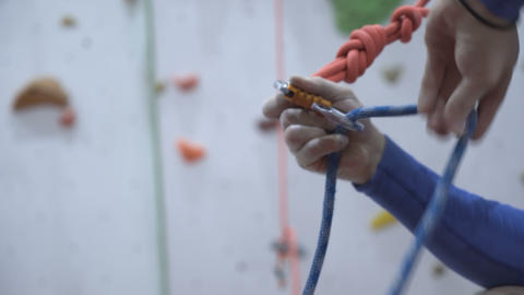 Man learns and practice to tie a knot near climbing wall indoors. Preparing Live Action