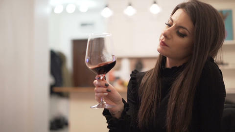 Brunette girl with red lipstick enjoying glass of red wine Live Action