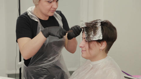 Professional hairdresser woman dyes girl's hair with hair dye on foil Live Action