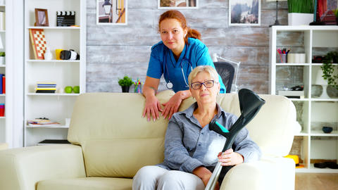 Pretty nurse in nursing home and old woman sitting on couch Live Action