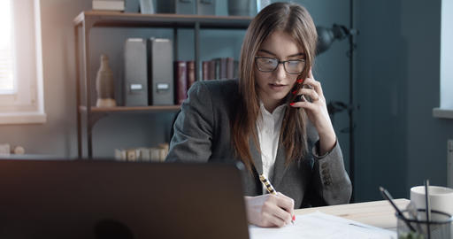 Female manager taking notes during conversation on phone Live Action