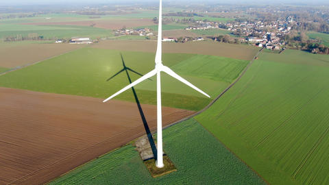 Aerial view of wind turbines on agricultural fields during blue winter day Live Action