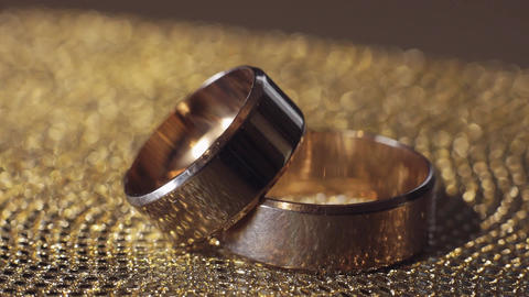 Wedding gold rings lying on shiny glossy surface. Shining with light. Close-up ライブ動画