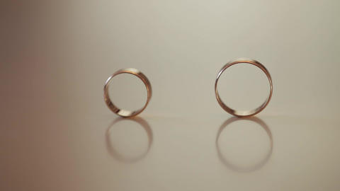 Wedding gold rings roll to each other. Close-up, macro shot ライブ動画
