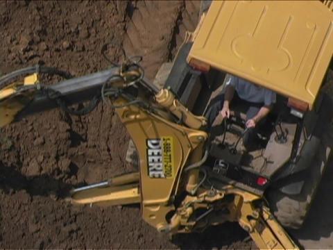 A John Deere Caterpillar moves dirt Stock Video Footage
